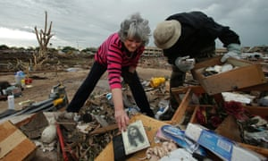 Lea Bessinger salvages a picture of Jesus as she and her son Josh Bessinger sort through the rubble of Lea's tornado-ravaged home.