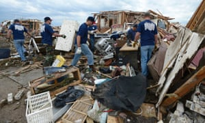 Firefighters help a fellow firefighter recover belongings from the rubble of his home.