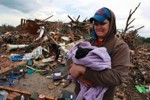 Austin Brock holds cat called Tutti, shortly after the animal was retrieved from the rubble of Brock's home, which was demolished a day earlier when a tornado moved through Moore. Photograph: Brennan Linsley/AP