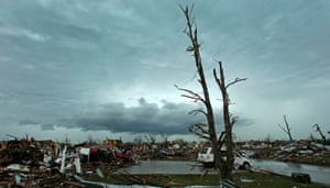 Storm clouds build in the distance beyond tornado-ravaged homes.
