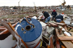 People search for belongings as water squirts from a water boiler in a destroyed neighborhood.