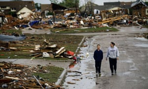 A woman and young boy walk along a street as they view destroyed house.