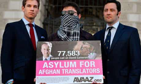 An Afghan interpreter with former British servicemen delivering a petition calling for asylum