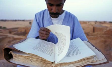 Curator Reading Koran on Roof of Library, Mauritania