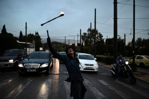 24 hours in pictures: Athens, Greece: A juggler performs at traffic lights
