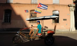 A tricycle taxi driver looks for customers as he flies Cuban and Venezuelan national flags in Havana.