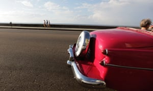 Also in Cuba, tourists ride a U.S.-made convertible car on Havana's seafront boulevard 'El Malecon'.