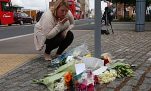 A woman blows a kiss as she lays flowers in memory of the victim outside the Royal Artillery Barracks near the scene of a terror attack in Woolwich.
