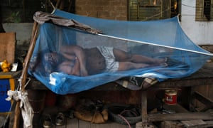 Back in a steaming India, a labourer sleeps on a makeshift bed covered with a mosquito net on a hot summer morning in New Delhi.