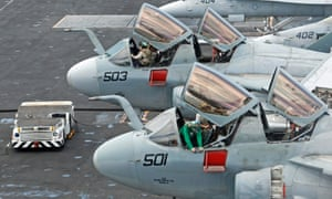 Maintenance personnel work in the cockpits of U.S. navy EA-6B Prowlers aircraft on the USS Nimitz aircraft carrier on patrol in the South China Sea.