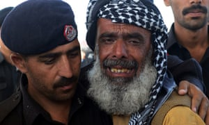 A Pakistani policeman comforts a mourner, during a funeral ceremony for policemen killed in a bomb attack  in Quetta this morning. A bomb planted in a rickshaw tore through a vehicle used by security forces in southwest Pakistan, killing at least 12 people, police said.