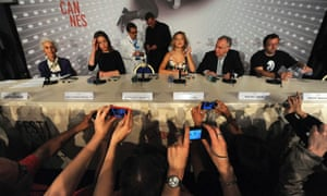 Journalists take pictures of cast members Lea Seydoux, Adele Exarchopoulos and director Abdellatif Kechiche as they arrive for a news conference for the film La Vie D'Adele during the Cannes Film Festival.