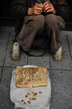 The hands of Virgilio, a 46 year old Lithuanian,  who was working on construction sites in Spain and has been unemployed for three years, rests on his knees, while he begs, with a sign reading 'no home no nothing', in Pamplona, northern Spain.