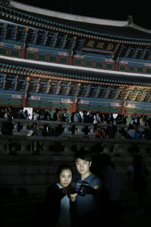 A couple takes a photograph of themselves during the evening at Gyeongbok palace in central Seoul, South Korea. The royal palace is offering late-night admissions to the public this week.