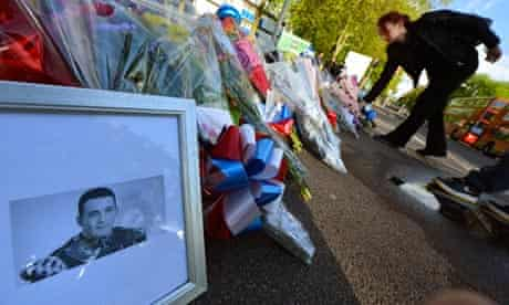 A picture of Drummer Lee Rigby is displayed with flowers outside an army barracks in Woolwich