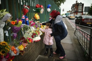 Members of the community lay flowers close to the scene where Drummer Lee Rigby of the 2nd Battalion the Royal Regiment of Fusiliers was killed, in London. Lee Rigby was murdered by suspected Islamists near London's Woolwich Army Barracks. For our live blog coverage click here. Photograph: Dan Kitwood/Getty Images