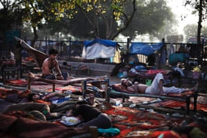 An Indian squatter sits as others sleep on rented cots at a public park near Jama Masjid, or the Grand Mosque, in New Delhi, India.
