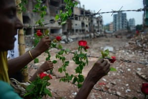 A Bangladeshi family member of a missing garment worker places roses on the barbed wire fence as she pays tribute to the victims at the site of the nine-storey building collapse in Savar, on the outskirts of Dhaka. Some 290 unidentified bodies were buried after DNA samples were collected to match those of relatives as the Bangladeshi army wrapped up its search for bodies at the site of the building collapse.