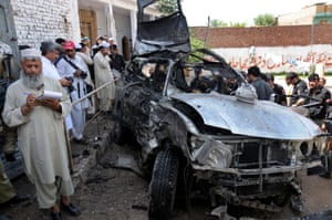 Pakistani policemen inspect the site of a suicide bomb blast that targeted a vehicle carrying Afghan religious leader Haji Hayatullah Khan at a seminary in Peshawar. Reports state that three persons were killed and two others injured when a blast targeted a vehicle carrying Afghan religious leader.