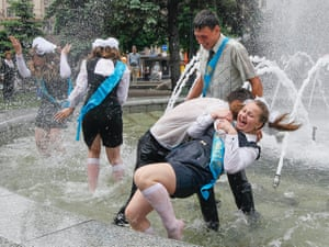 Ukrainian students fool around in a fountain as they celebrate the end of their school term at the Independence square in downtown Kiev.