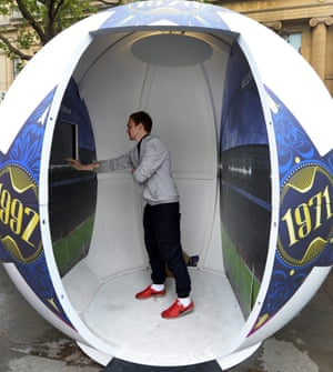 And a fan tries out a football shaped interactive photo booth at the UEFA Champions League fan zone at Trafalgar Square in London. Photograph: Andy Rain/EPA