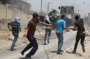 Deja vu: Palestinian protesters throw stones towards an Israeli bulldozer during clashes following a protest against the expropriation of Palestinian land by Israel in the village of Kafr Qaddum, near the occupied West Bank city of Nablus.
