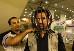 An Iraqi man wears a torture device used by the regime of Iraq's ousted leader Saddam Hussein at the Shaheed Monument in Baghdad.