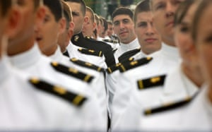 A member of the 2013 graduating class of the United States Naval Academy peeks over the shoulder of a fellow graduates to listen to President Barack Obama during the commencement ceremony at the Academy in Annapolis. The president urged new graduates to exhibit honor and courage in tackling incidents of sexual assault as they assume leadership positions in the military.