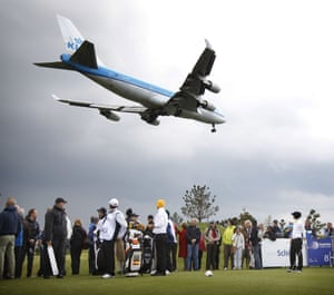 Meanwhile across the sea a Dutch golfer Christel Boeljon (R) awaits her turn until the plane has landed during the women's Open golf tournament on the International Golf Course in Amsterdam.