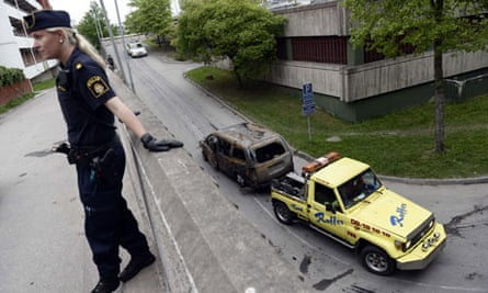 A police officer stands guard after youths rioted in Husby, northern Stockholm