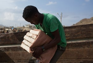 FTA: Siegfried Modola : A man lifts slabs of salt onto a truck in the town of Berahile in Afar, nor