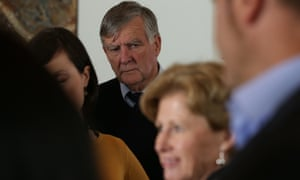 Senator Bill Heffernan photobombs Greens Leader Christine Milne at a doorstop interview in the Mural Hall of Parliament House.