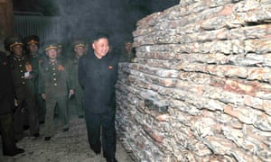 North Korean leader Kim Jong-un smiles (or winces) as he inspects a fishery station under the Korean People's Army Unit.