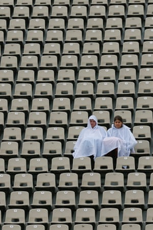Lonely and soggy spectators wait as the tennis is delayed by rain during day two of the French Open in Paris.