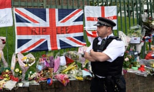A police officer stands near tributes to soldier Lee Rigby outside the Royal Artillery barracks at Woolwich. The suspects in his death are currently in custody in hospital in a stable condition after being shot and wounded, but have yet to be questioned.