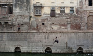 An Indian youth jumps into the Nizamuddin Baoli, a stepwell built circa 1321-1322 that holds water from an underwater spring, on a hot day in New Delhi, India. Temperatures in the Indian capital peaked at 44 degrees Celcius.