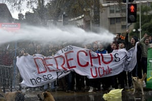 Watered down education: Chilean students are sprayed by a water cannon during clashes with riot policemen at a protest to demand Chilean President Sebastian Pinera's government to improve the public education quality, in Santiago.