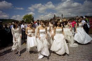 Newly married brides walk across the Charles Bridge in Prague, Czech Republic.