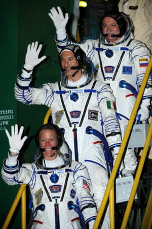 Members of the expedition Russian cosmonaut Fyodor Yurchikhin (top), US astronaut Karen Nyberg (bottom) and Italian astronaut Luca Parmitano (C), wave during the farewell ceremony before boarding the spacecraft Soyuz TMA-09M at Baikonur cosmodrome in Kazakhstan.