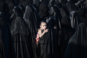 A Bahraini girl is carried by her mother during the funeral of Sayed Omran Sayed Hameed, in the village of Karzakkan, south of Manama.