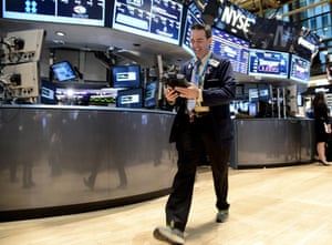 A rather pleased looking trader work on the floor of the New York Stock Exchange (NYSE) in New York, United States. The Dow Jones Industrial Average rose 106.29 points, or 0.69%% per cent, to close at 15409.39 a record high.