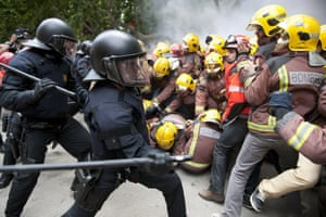 Riot police try to stop the entrance to the Catalonia Parliament at firemen protesting for sector budget cut in Barcelona.