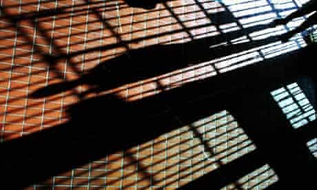 The shadow of a man and prison bars stretches across a tiled floor