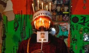 Rajendra Kumar Tiwari, an Indian social activist, poses with burning candles and a photo of Sarabjit Singh