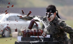 A commando shows off his skills  as he smashes bottles in a performance for children in Gyeryong City, South Korea