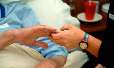 hospice worker holding patient's hand