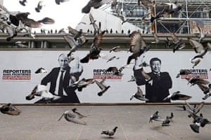 24 hours in pictures: Pigeons fly past a poster depicting Vladimir Putin and Xi Jinping