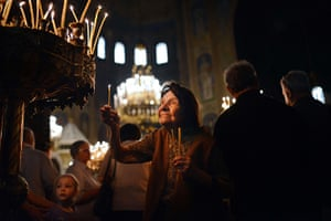 24 hours in pictures: A Bulgarian woman lights a candle during the Good Friday s