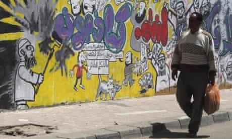 A man walks past graffiti depicting the Muslim Brotherhood along Mohamed Mahmoud Street in Cairo