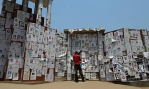 A man holds a photograph of his wife in front of  a wall filled with photos of garment workers who are still  missing after the Rana Plaza building collapsed
